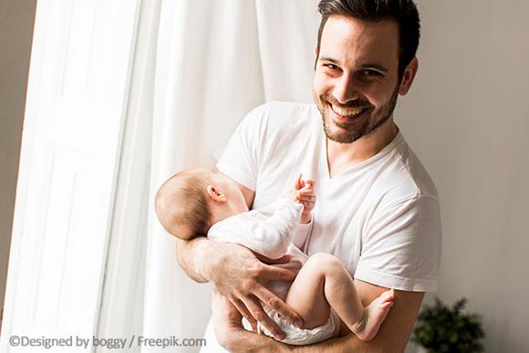 Vater hält Baby vor der U3 Untersuchung.
